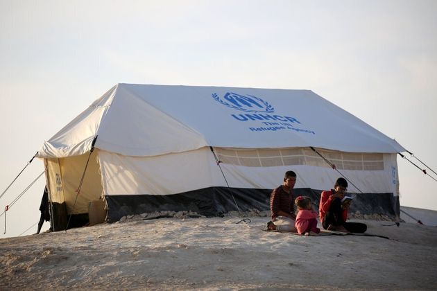 Youth sit outside a UNHCR tent at a refugee camp housing Iraqi families who fled fighting in the Mosul