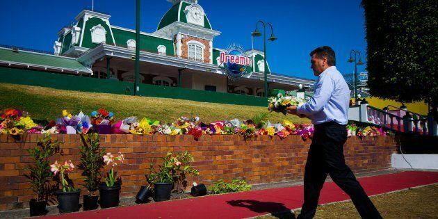Dreamworld CEO Craig Davidson lays flowers at a makeshift floral tribute at the theme park on the Gold...