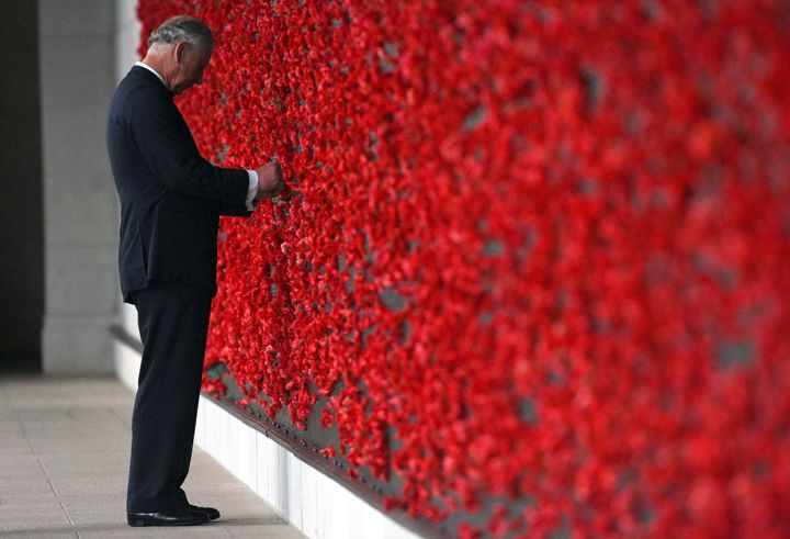 Prince Charles placing a poppy onto the Roll of Honour wall during the 2015  Remembrance Day ceremony at the Australian War Memorial in Canberra.