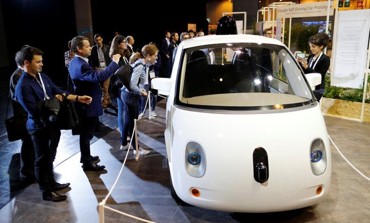 Visitors look at a self-driving car by Google displayed at the Viva Technology event in Paris in 2016.