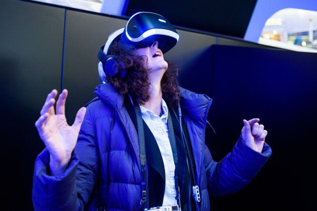 A woman wears a PlayStation VR headset.