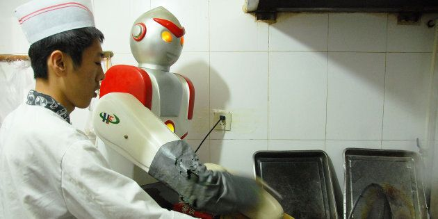 BEIJING, CHINA - APRIL 14: An Ultraman-shaped robot makes shaved noodles in 10 seconds. It's been working...
