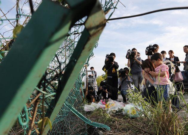 保育園児らの列に乗用車が突っ込んだ事故で、フェンスが大きく変形した現場に花を手向ける人たち=5月8日午後、大津市