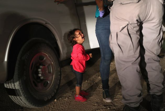 A two-year old Honduran asylum seeker cries as her mother is searched by border patrol agents. Under...