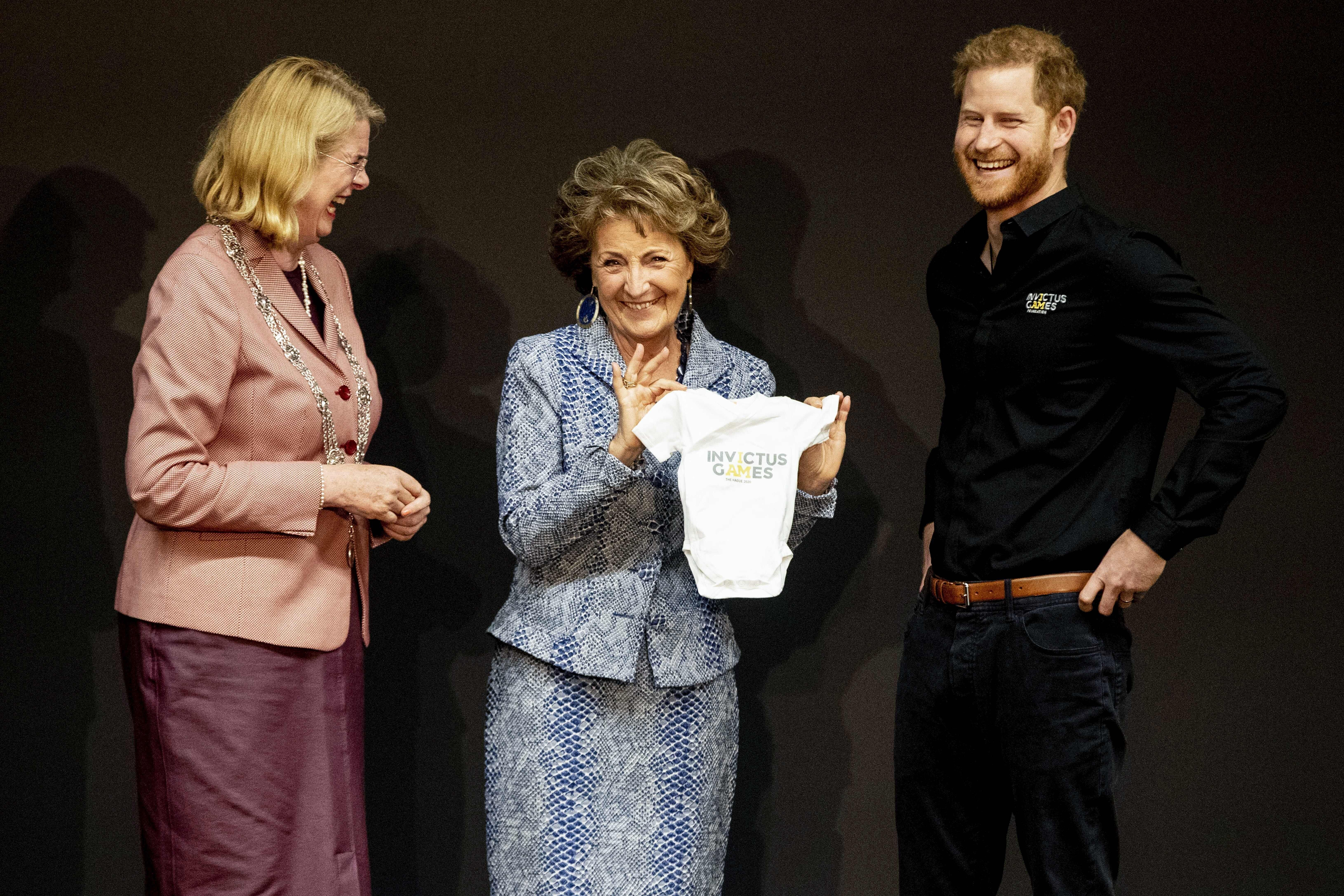 Netherlands' Princess Margriet (center) holds a piece of baby clothing next to Britain's Prince Harry (right) during the pres