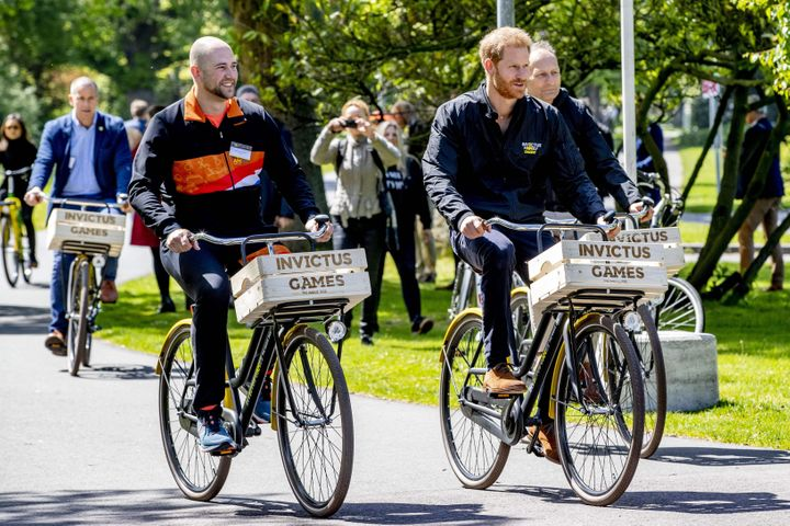 Former Dutch serviceman and athlete Dennis van der Stroom (left) and Prince Harry (right) ride bikes during the presentation