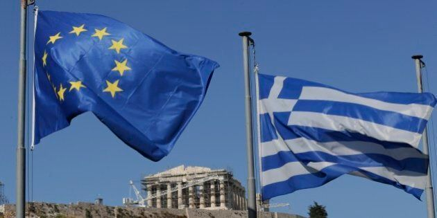The Greek, right, and the European flags wave under the ancient Acropolis hill in Athens, Sunday, July...