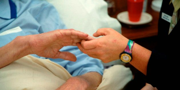 Hospice worker holding elderly man's hand UK. (Photo by: Photofusion/UIG via Getty