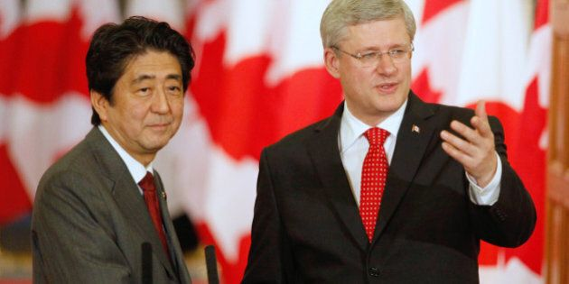 Prime Minister of Canada Stephen Harper(R) and Prime Minister of Japan Shinzo Abe shake hands a joint...