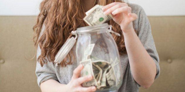 USA, Utah, Salt Lake City, Young woman putting money into her savings jar