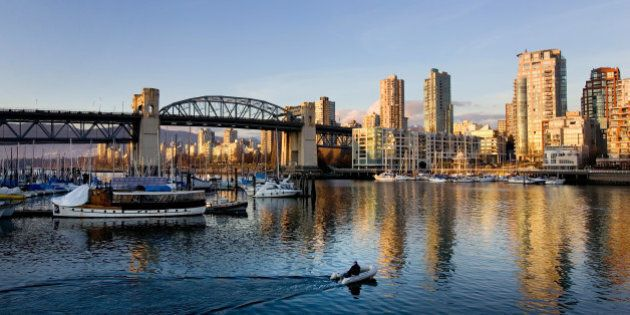 VANCOUVER, CANADA - FEBRUARY 18: A boater motors towards the Burrard street bridge as the sun sets on...