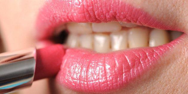 woman putting pink lipstick
