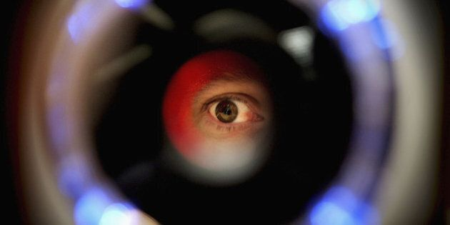 LONDON - OCTOBER 14: A man uses an iris recognition scanner during the Biometrics 2004 exhibition and...