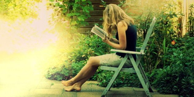 young woman reading outside in beautifully lit green summer garden