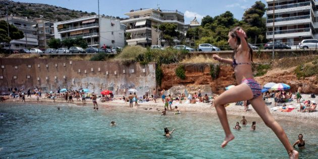 ATHENS, GREECE - JUNE 28: People swim and jump in the water at the beach on June 28, 2015 in Athens,...