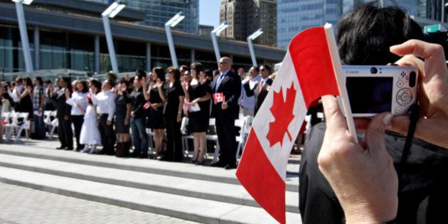 A woman takes a photograph while holding a Canadian flag as a group of 61 new Canadians take the oath...