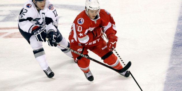 Western Conference's Brian Connelly (10), of the Abbotsford Heat, tries to keep the puck away from Eastern...