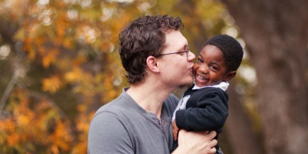 Father kissing his adopted toddler son who is African-American at Old Settler's Park in Round Rock,