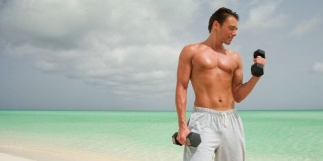 Man on beach doing biceps curls with dumbbells