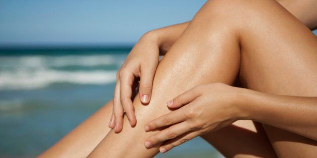 Woman rubbing legs, low