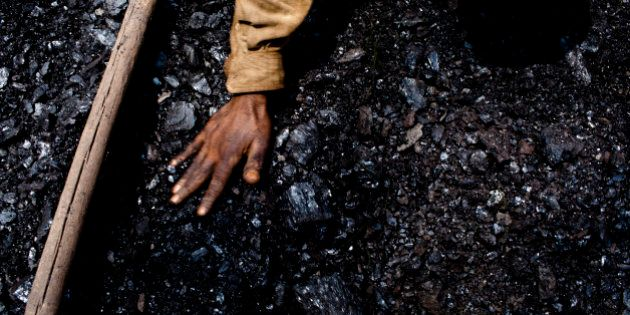 JAINTIA HILLS, INDIA - APRIL 16: Thirty eight-year-old Prabhat Sinha, from Assam, levels out the coal...