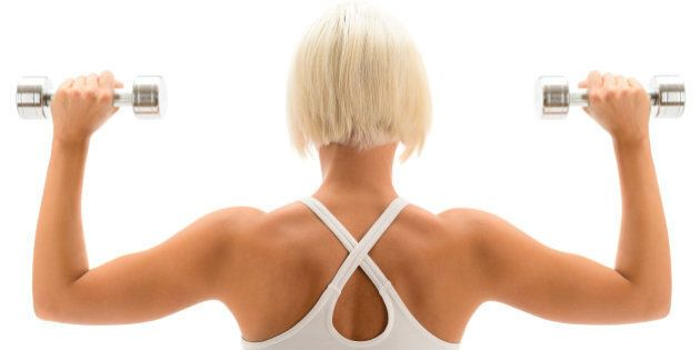Back view portrait muscular blond woman holding dumbbell on