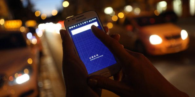 BERLIN, GERMANY - SEPTEMBER 02: In this photo illustration, a woman uses the Uber app on an Samsung smartphone...