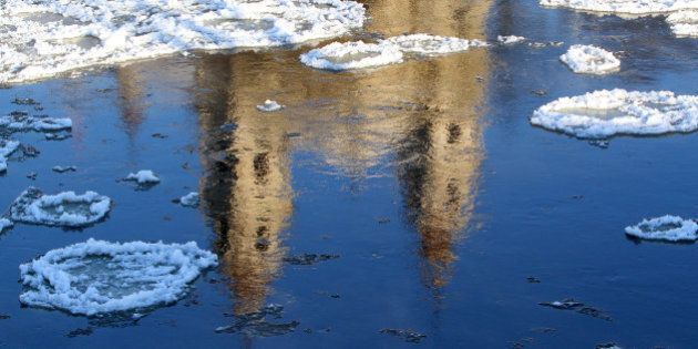 The church of St Philip and St James reflects on the frozen river Neris in Vilnius, Lithuania on January...
