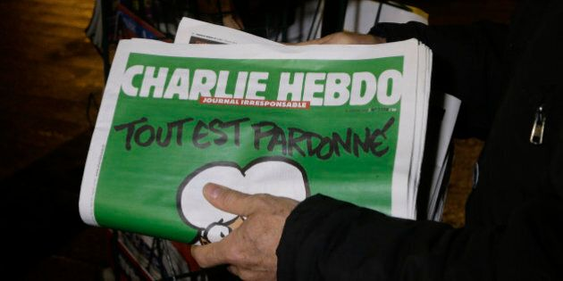 A seller of newspapers installs in shelf, several Charlie Hebdo newspapers at a newsstand in Nice southeastern France, Wednesday, Jan. 14, 2015. On front page reading