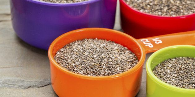 chia seeds in colorful measuring cups against slate rock