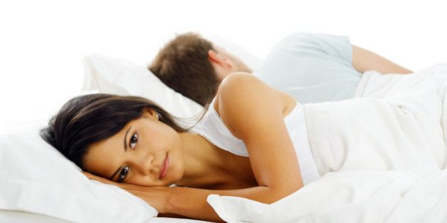 Unhappy couple lying in bed facing away from each other after and argument or