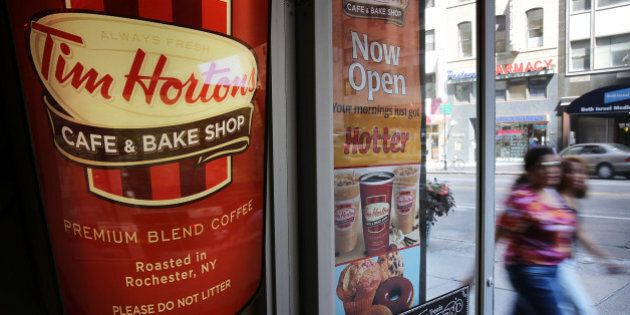 NEW YORK, NY - AUGUST 25: People walk past a Tim Horton's cafe in Manhattan on August 25, 2014 in New...