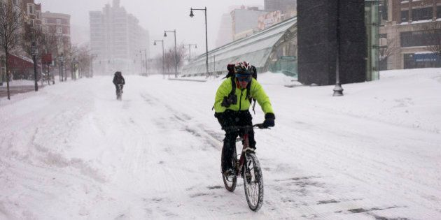 BOSTON, MA - JANUARY 27: Two bicyclists travel over snow January 27, 2015 along an empty Commonwealth...