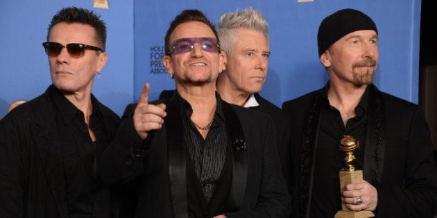 From left, Larry Mullen Jr., Bono, Adam Clayton, and The Edge of U2 pose in the press room with the award...