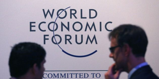 Attendees pass a World Economic Forum logo as they walk through the Kongress Zentrum, or Congress Center,...
