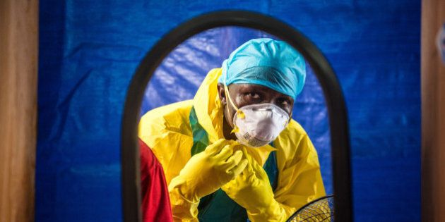 FILE - In this Thursday, Oct. 16, 2014 file photo, a healthcare worker dons protective gear before entering an Ebola treatment center in the west of Freetown, Sierra Leone. (AP Photo/Michael Duff, File)