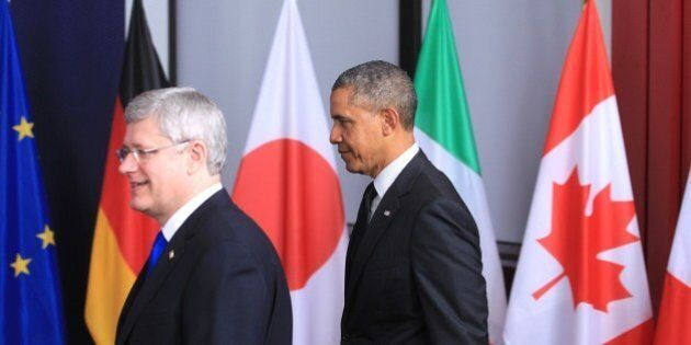 U.S. President Barack Obama, right, and Canadian Prime Minister Stephen Harper walk together to a group...