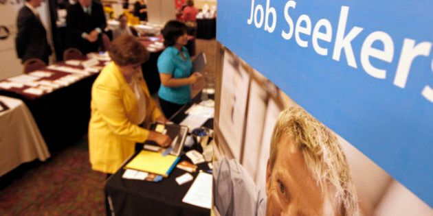In this Tuesday, July 10, 2012 photo, people walk by the recruiters at a jobs fair in the Pittsburgh...