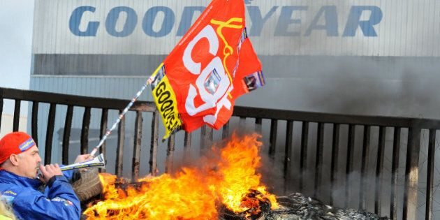 An employee waves a flag and blows a horn next to burning tyres in front the US Goodyear tyremaker site...