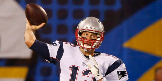 New England Patriots quarterback Tom Brady throws during warm ups before facing the San Diego Chargers...