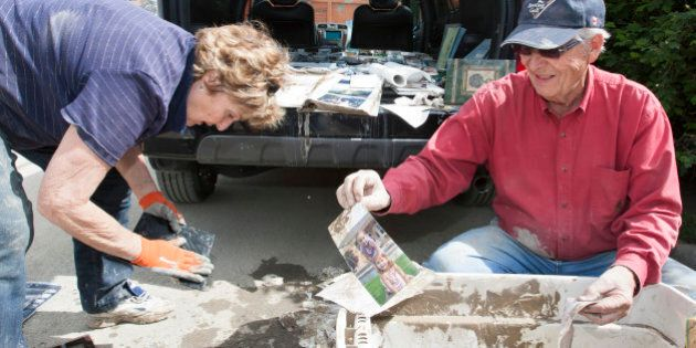 Carol Armstrong, left, and Don Armstrong sort through water-damaged photographs as they help clean their...
