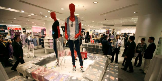 Guests look around interior of the largest global flagship store of Uniqlo during its pre-opening Thursday,...