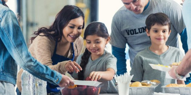 Young Hispanic family is serving healthy meals to people in charity food bank soup kitchen. Mother and father are instructing elementary age little boy and little girl as they serve food to senior man and preteen girl.