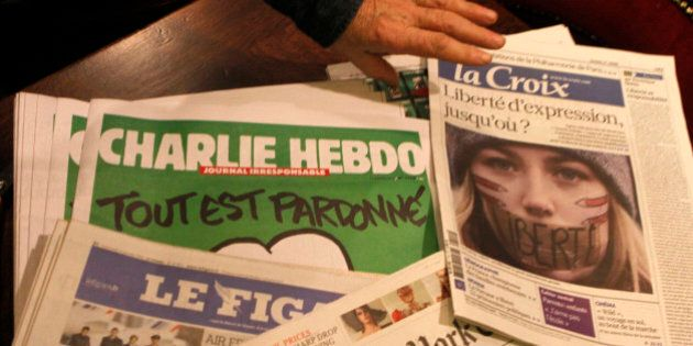 Copies of the latest issue of Charlie Hebdo newspaper are sold with other newspapers at a newsstand in...