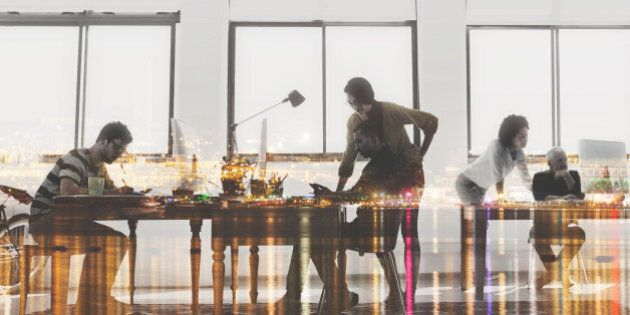 Multiple exposure shot of colleagues working in a modern office superimposed over a city