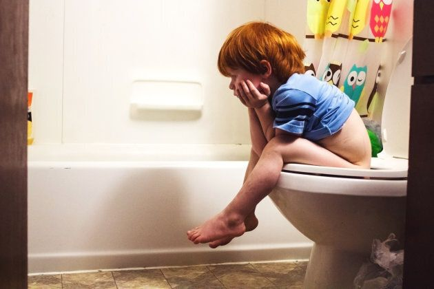 Young boy sitting on the toilet