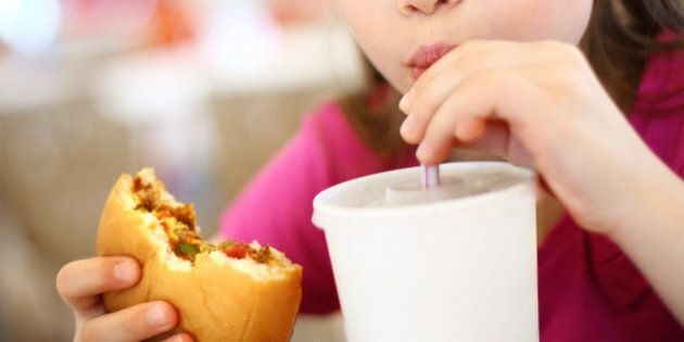 Closeup of little girl eating burger and drinking soda. Cut for unrecognition.The girl is elementary age and wearing pink t-shirt