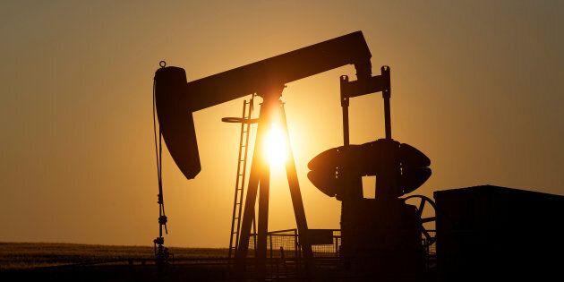 An oil pump jack pumps oil in a field near Calgary in