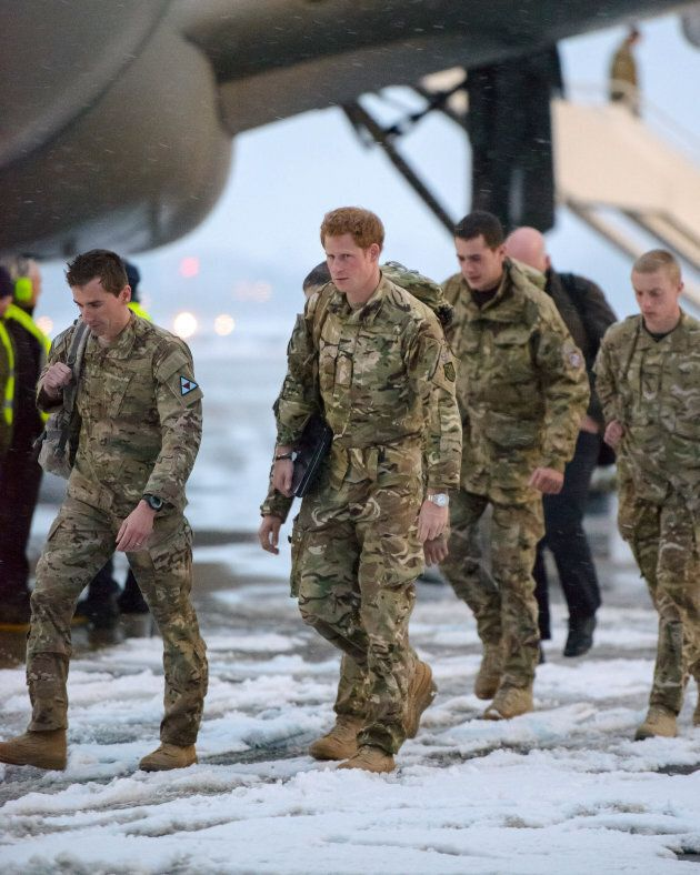 Britain's Prince Harry walks after disembarking from a Voyager transport aircraft at RAF Brize Norton,...