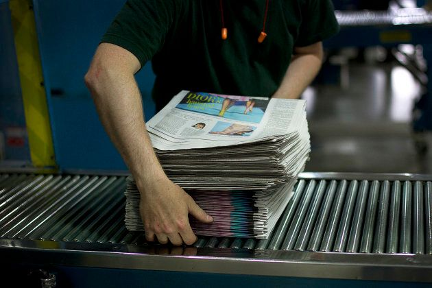 An employee stacks newspapers at the Toronto Star printing plant in Toronto, Ont., July 6,